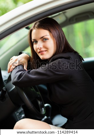 Portrait of a young woman resting her head on the steering wheel