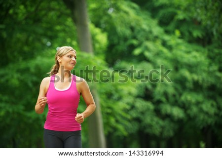 Portrait of a young woman running alone in the park - stock photo