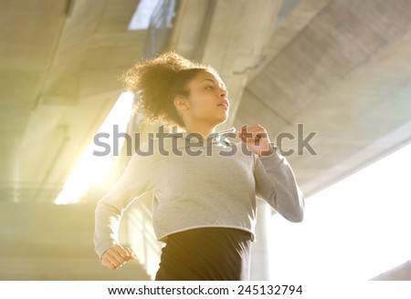 Portrait of a young woman running in urban environment - stock photo