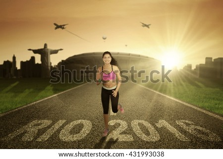 Portrait of a young woman running on the road with text of Rio 2016 on the asphalt. Shot with stadium background