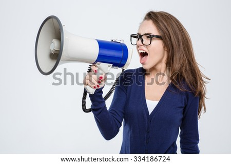 Portrait of a young woman screaming in megaphone isolated on a white background - stock photo