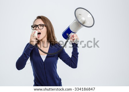 Portrait of a young woman screaming in megaphone isolated on a white background