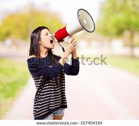 portrait of a young woman screaming with a megaphone at a park - stock photo