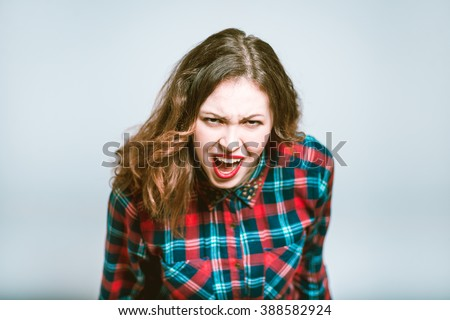 Portrait of a young woman shouting angry, isolated on a gray background - stock photo