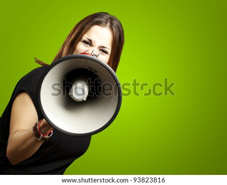 portrait of a young woman shouting with a megaphone over a green background