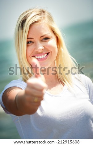 Portrait of a young woman showing a thumbs up sign, vivid colors - stock photo