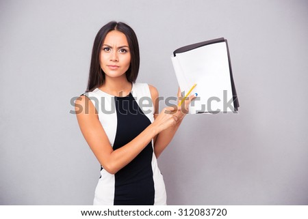 Portrait of a young woman showing contract over gray background - stock photo