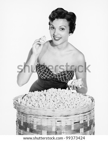 Portrait of a young woman showing popcorn and smiling - stock photo