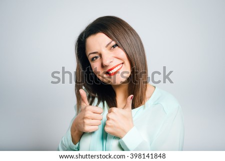 Portrait of a young woman shows like this, thumbs up - stock photo