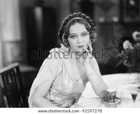 Portrait of a young woman sitting at a table and thinking in a restaurant
