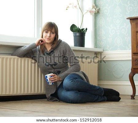 Portrait of a young woman sitting at home with a cup of tea - stock photo