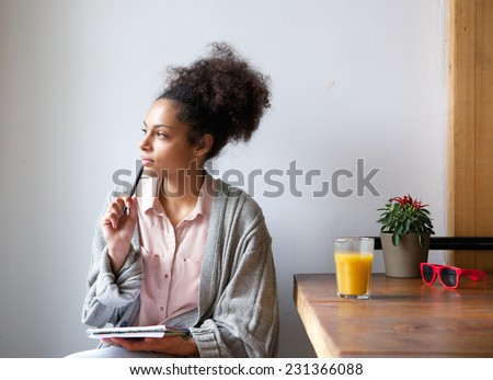Portrait of a young woman sitting at home with pen and paper - stock photo