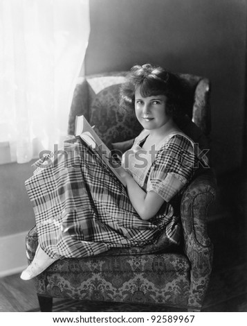 Portrait of a young woman sitting in an armchair and holding a book - stock photo