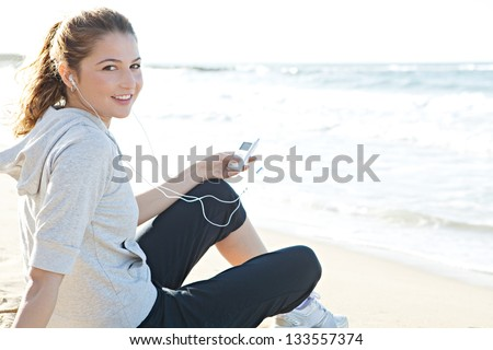 Portrait of a young woman sitting on a white sand beach shore, holding a music player and listening to music with her head phones, turning and smiling at the camera.