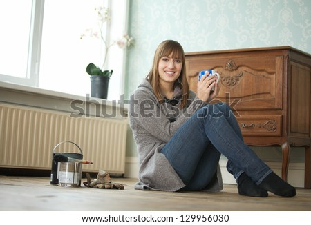Portrait of a young woman sitting on floor and holding tea cup - stock photo