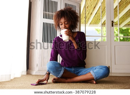 Portrait of a young woman sitting on floor at home with coffee and mobile phone