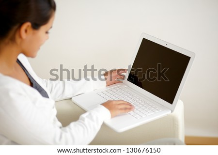 Portrait of a young woman sitting on sofa and working on laptop computer at home - stock photo