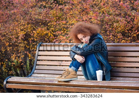 Portrait of a young woman sitting on the bench with closed eyes in autumn park