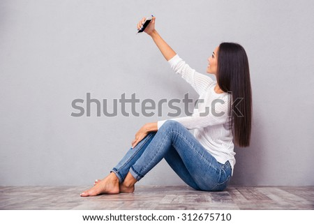 Portrait of a young woman sitting on the floor and making selfie photo on smartphone on gray background - stock photo