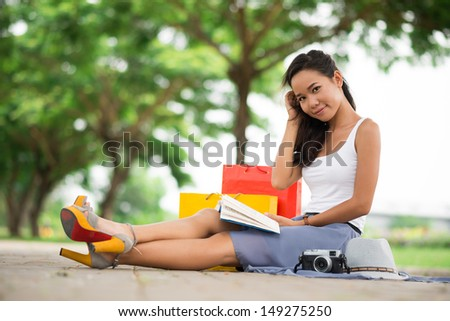 Portrait of a young woman sitting on the ground in the park and reading - stock photo