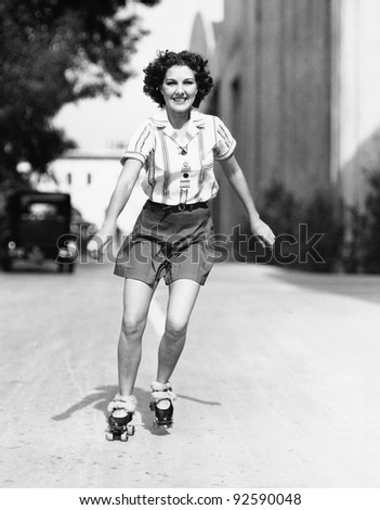 Portrait of a young woman skating on the road and smiling - stock photo
