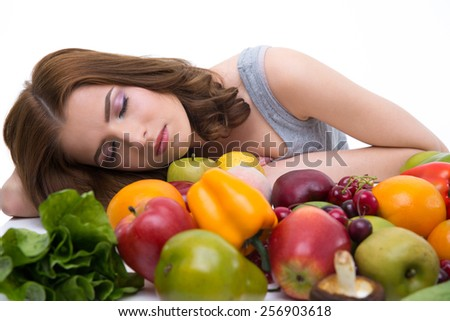 Portrait of a young woman sleeping on the table with many fruits - stock photo