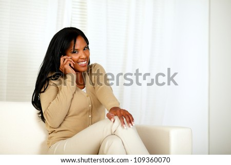Portrait of a young woman smiling at you while speaking on mobile phone at home indoor - stock photo