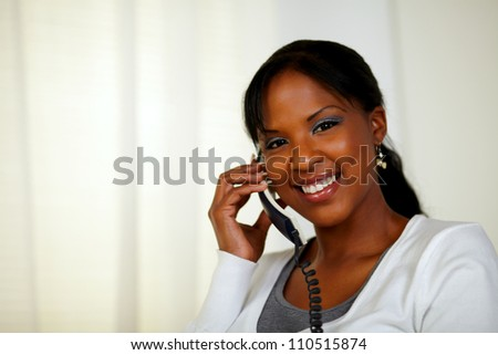 Portrait of a young woman smiling at you while talking on phone at soft colors composition