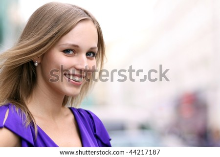 Portrait of a young woman smiling on urban background - stock photo