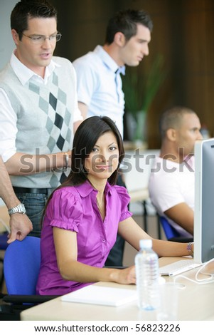 Portrait of a young woman smiling sitting in front of a desktop computer - stock photo