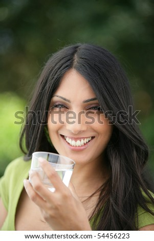Portrait of a young woman smiling with a glass of water