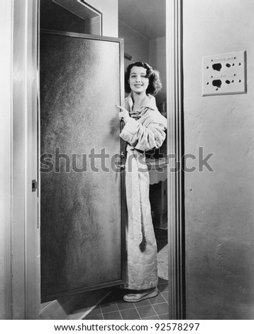Portrait of a young woman standing at a door of a bathroom - stock photo