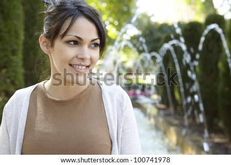 Portrait of a young woman standing in a park beside a fountain with flowing water, smiling. - stock photo