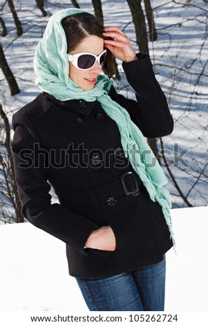 Portrait of a young woman standing in snowy winter forest, wearing scarf on her head, sunglasses, looking down