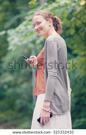 Portrait of a young woman standing in the forest and holding mobile phone - stock photo