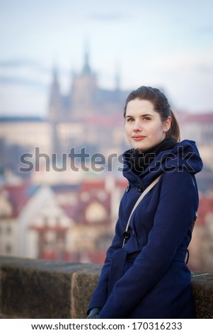 Portrait of a young woman standing on the Charles Bridge with the panorama of Prague Castle in the background (Prague, Czech Republic)