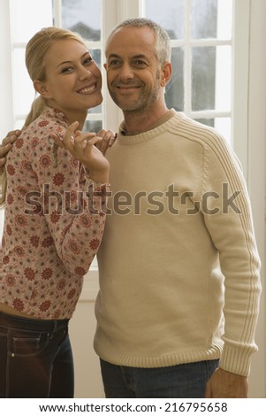 Portrait of a young woman standing with a mid adult man and smiling