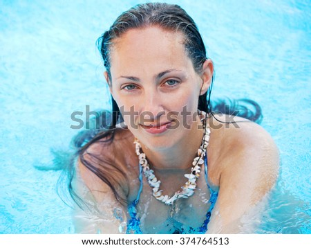 Portrait of a young woman swimming at the pool, horizontal view, outdoors shot