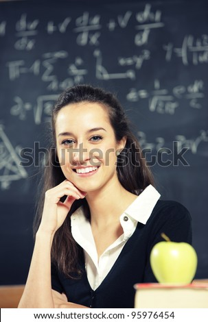 Portrait of a young woman, teacher in front of a blackboard - stock photo