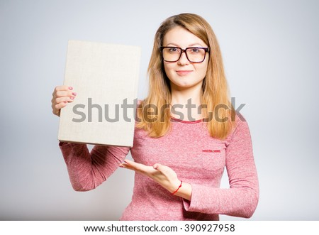 Portrait of a young woman teacher showing a book, isolated on a gray background - stock photo