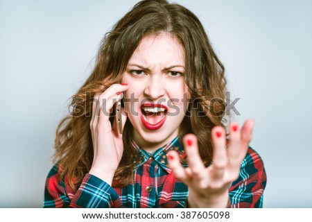 Portrait of a young woman, the bad news over the phone, isolated on a gray background - stock photo
