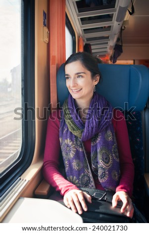 Portrait of a young woman traveling by train - stock photo