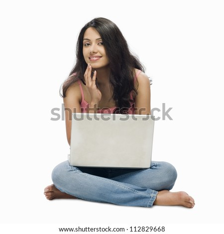 Portrait of a young woman using a laptop - stock photo