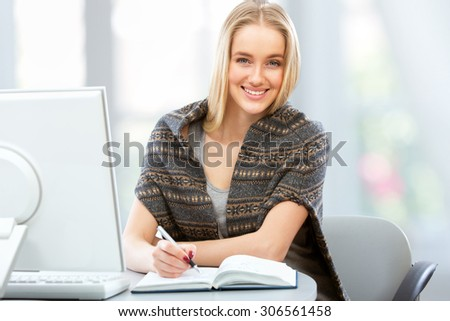 Portrait of a young woman using computer at home - stock photo