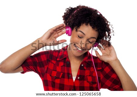 Portrait of a young woman using pink headphones and enjoying pleasant musical world.