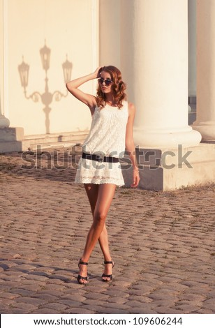 Portrait of a young woman walking on the streets of old european city. Outdoors - stock photo