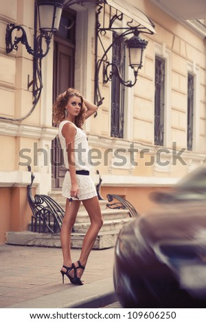 Portrait of a young woman walking on the streets of old european city. Outdoors