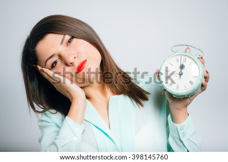 Portrait of a young woman wants to sleep with a retro alarm clock - stock photo