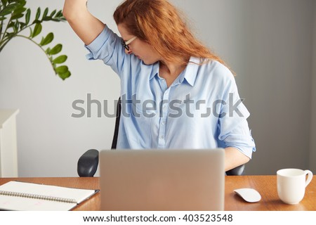 Portrait of a young woman wearing blue shirt disgusting with bad smell of her wet armpit while working in the office. Something stinks, negative human emotions, facial expressions, feeling reaction - stock photo