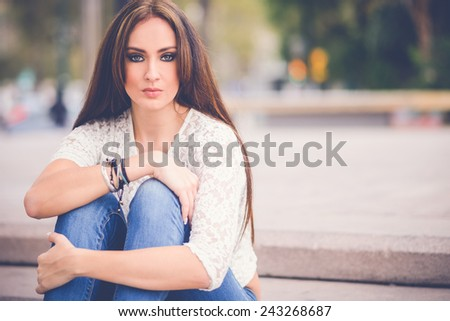 Portrait of a young woman, wearing casual clothes, with long hair in urban background